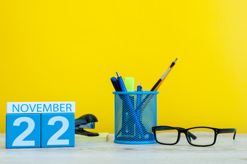 November 22nd. Day 22 of month, wooden color calendar on yellow background with office supplies. Autumn time