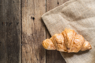 fresh butter croissant on gunny sack cloth on wooden table with copy space, top view
