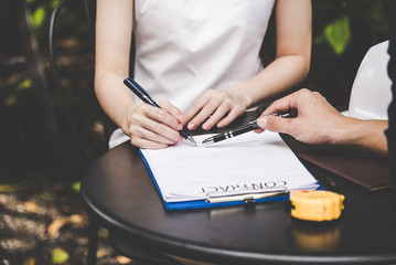 Woman hand signing a contract for building house with architect man.  Contract Concept.