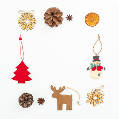 Christmas decoration - tree, snowflakes, snowman and pine cones on white. Flat lay, top view. New Year frame concept.