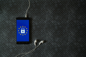 General Data Protection Regulation (GDPR) on smartphone and earphones placed on metal plate