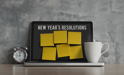 New Year resolutions, notes, goals, post, memo or action plan concept. Sticky notes (for input text) on laptop in workplace office with clock and coffee on wooden desk and loft wall.