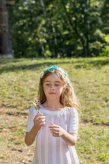 Cute little girl walking in the city park on a sunny summer day
