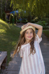 Cute little girl in a funny hat posing in the city park on a sunny summer day