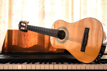 Guitar on piano keyboard. Classical music instrument. Sepia and warm color tone. Art and music background.