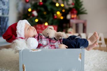 Christmas portrait of cute sleeping newborn baby boy, dressed in christmas clothes