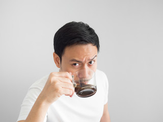 Man in white t-shirt drinks a cup of coffee.