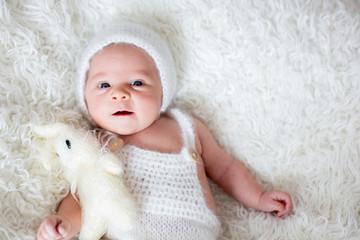 Beautiful newborn baby boy, looking curiously at camera