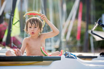 Cute little child, boy, eating watermelon on the beach