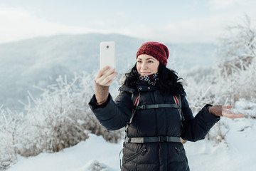 Smiling female tourist dressed warm taking a selfie in a snowy country