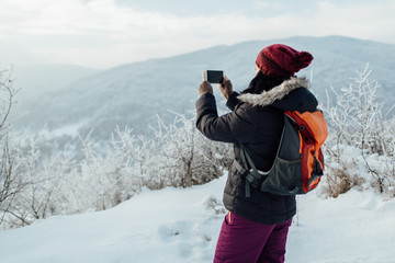 Rear view of a woman dressed warm taking pictures of snowy hills.