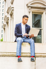 African American college student studying in New York, wearing blazer, gray pants, red socks, sneakers, sitting on street outside office building, looking down, reading, working on laptop computer. .