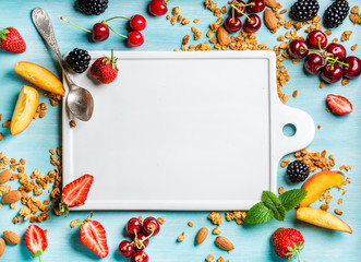 Healthy breakfast ingredients. Oat granola, fruit, berries and mint on blue background with white ceramic board in center, top view, copy space