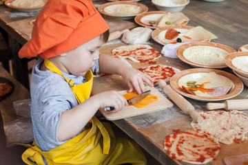Tuinposter Koken Little cook. Children make pizza. Master class for children on cooking Italian pizza. Young children learn to cook a pizza. Kids preparing homemade pizza