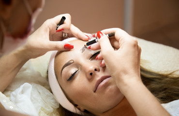 Beautiful woman getting her eyebrows done at a beauty salon.