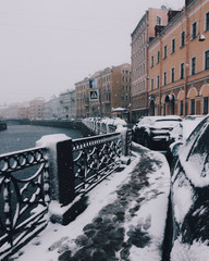 Outdoor view of busy city with traffic jam, many cars and snow, frozen river with bridge. City lamdscpae. Picture of snowy city or town, many bilduings in background