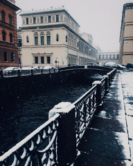 Beautiful view of frozen river and bridge, nice city with ancient bilduings. Calm snowy town, wonderful landscapes. Winter, season, atmospehere and snowfall.