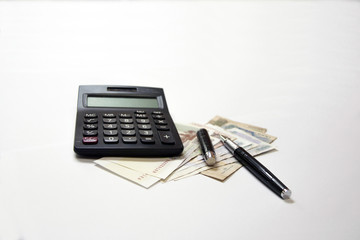 Black calculator and black metal pen on the Cambodian banknote isolated on white background. Concept of business and finance.