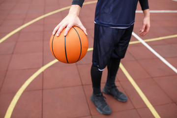 A guy is holding a basketball on the court