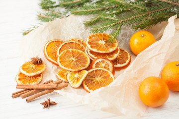Dried oranges and cinnamon sticks with snow-covered fir branch