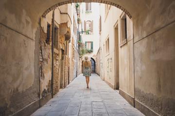 Rear view of woman walking in narrow footpath amidst buildings