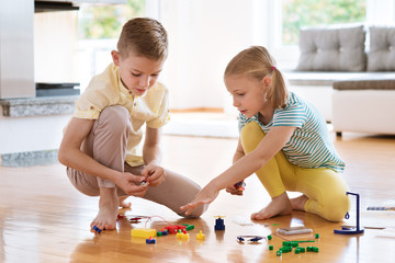 Two curious happy children playing with game