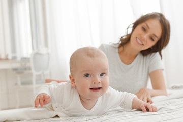 Mother and baby playing and smiling on the bed happy family. Boy looking at camera