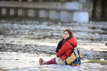girl travel in kyoto, siting near the riverband