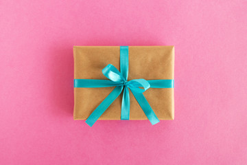 Gift box wrapped of craft paper and blue ribbon on the pink background, top view.