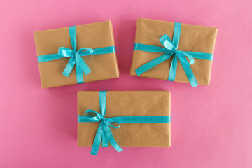 Three gift boxes wrapped of craft paper and blue ribbon on the pink background, top view.