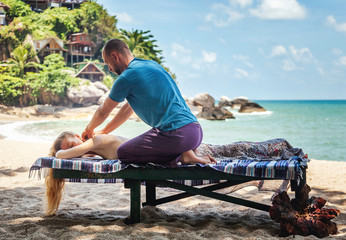 Therapeutic massage on the shore of the tropical sea. Travel, health, relaxation, pleasure