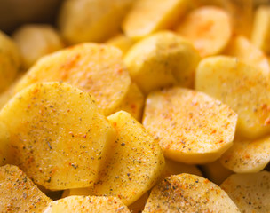 Raw potatoes prepared for baking with flavorings and cheese on tray.