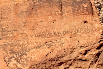 Inscription on red rocks in the valley on Wadi Rum desert in Jordan