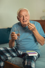 Senior Man Sitting On Bed At Home Taking Medication
