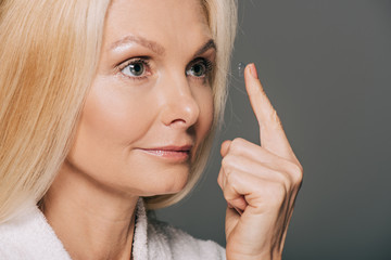 mature woman applying contact lens