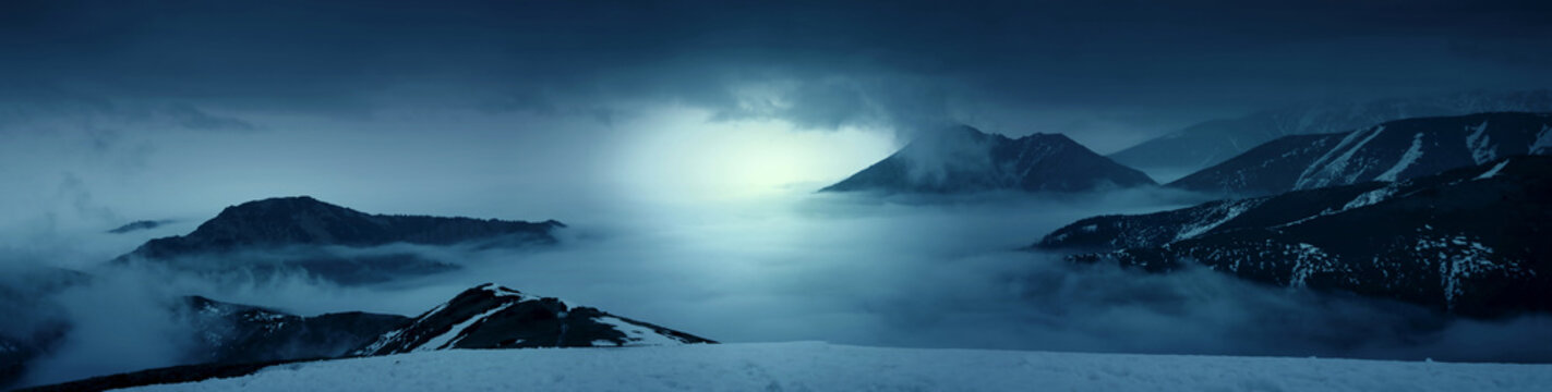 Fantasy photo of a mountains in the mist at evening. White lights. Magic and scenic landscape photo