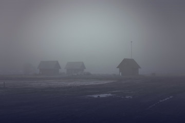 The wooden houses on a dark background. A fog on the edge of the forest and fields. The landscape of horror