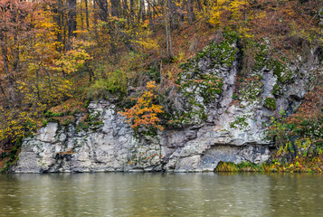rocky cliff above the river in autumn forest. stunning nature scenery