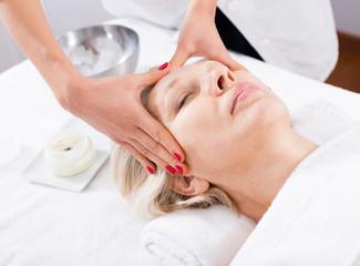 Mature woman having face massage
