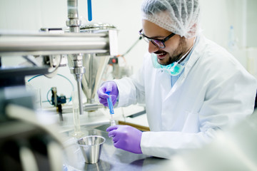 Young smiling researcher with gloves and hair protection working with syringe and tubes at the lab table.