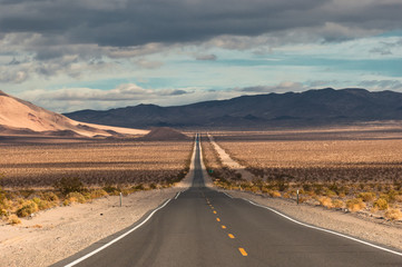 Classic long desert highway leading into the wild desert landscape of Death Valley National Park Wall mural