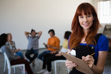 Portrait of smiling teacher holding clipboard with students