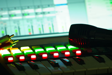 Blurred closeup of music recording studio instruments, with gears for electronic and digital music composition. Blur and instragram colors effect applied. Background for music industry and tech news.