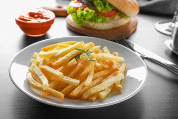 Plate with yummy french fries on table
