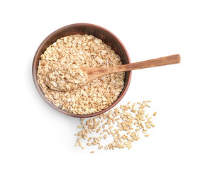 Bowl with raw oatmeal and spoon on white background