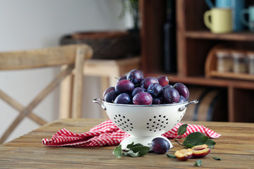 Fresh plums in colander on table
