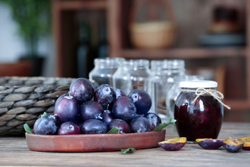 Tray with plums and jar of jam on table