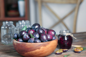 Bowl with plums and jar of jam on table