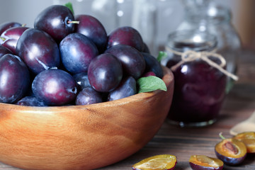 Bowl with plums on table, closeup