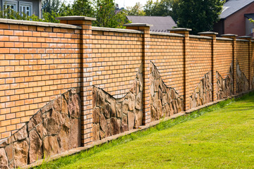 fence of stone and green lawn